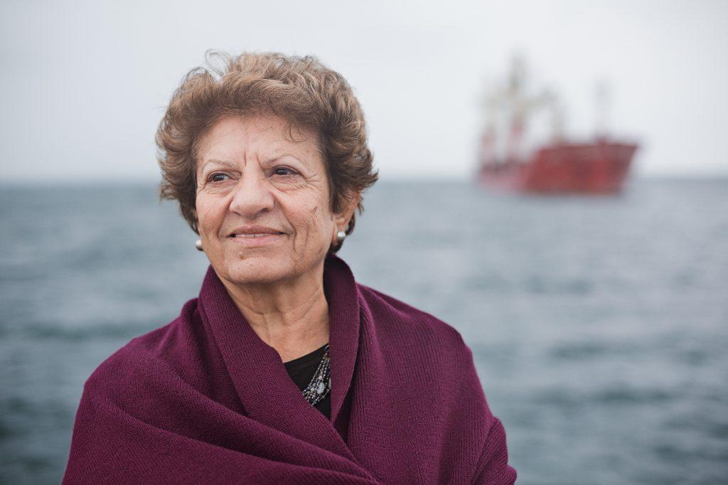 Jean Zaru, kvinna i 70årsåldern, kort mörkblont lockigt hår, iförd mörklila sjal, svart överdel och ett halsband sticker fram, havet i bakgrunden och en röd lastbåt i oskärpa till höger i bilden, Jean blickar ut åt vänster