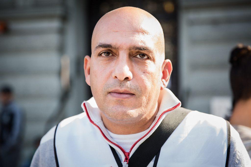Närbild på Mohammed Al Sayed som ser sorgsen ut, är i 40årsålden, rakad på huvudet, kort skäggstubb, vit tjocktröja med röd dragkedja. Bilden är tagen med kort skärpedjup, bakgrunden i oskärpa, några människor skymtas och en mörkgrå husfasad. Solljus snett bakifrån på Mohammeds vänsterkind.