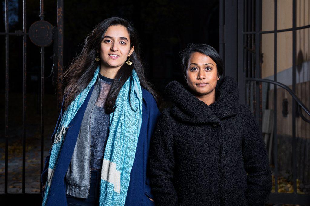 Farida i öppen blå kappa och ljusblå halsduk, Mahi i svart vinterjacka, bilden tagen utomhus på kvällen, Farida och Mahi är upplysta med blixt, mörk bakgrund.