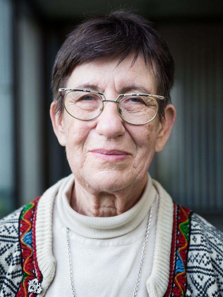 Karin Utas Carlsson, vit kvinna i 60årsåldern, kortbrunt hår, glasögon, vit polotröja, kofta utanpå, närbild, kort skärpedjup, allvarligt men vänligt uttryck
