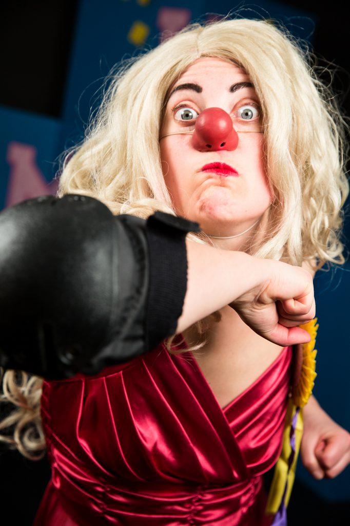 Miss Weltmeister, en clown med vit hudfärg, lång ljusblond peruk, röd clownnäsa, rött läppstift och röd klänning. Halvbild. Hon har höger armbåge framåt mot kameran, munnen är sned och ögonen uppspärrade. Höger hand i nederkant av bilden knuten liksom vänster. Bilden tagen med blixt, mörk bakgrund, scenografi skymtas.