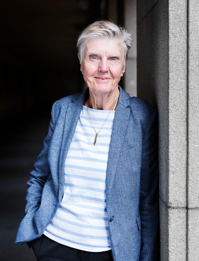 Barbro Westerholm står lutad mot grå pelare, i övrigt mörk bakgrund, blå kavaj, ljus tröja, svarta byxor, halvbild. Ser självsäker, lugn och tillitsfull ut.