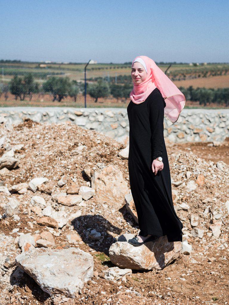 Yasmine står på en sten, i bakgrunden landsbyggd. Den svarta hellånga klänningen vajar i vinden liksom hennes rosa hijab. En modern klocka på vänsterarmen.