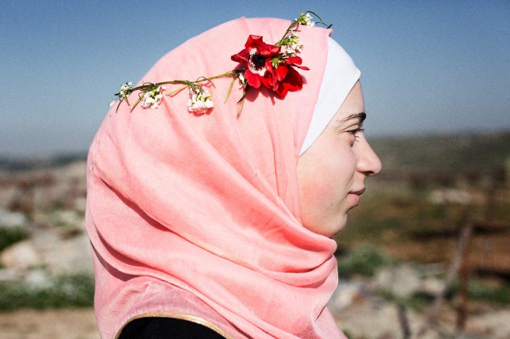Yasmine står i profil, tittar åt höger, har ljusrosa hijab och en något vissen tunn blomsterkrans på huvudet med röd valmo och vita små blommor. Avslappnat ansiktuttryck.