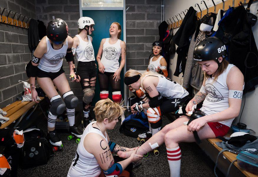 Sju roller derby-spelare i omklädningsrummet. I förgrunden lägger en spelare bandage om en annans fot, bakom står två och skrattar med varandra.