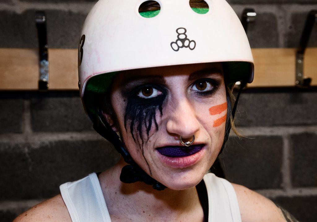 Porträtt Tiny Terror, sminkad svart runt ögonen. Runt höger öga har färgen som runnit ner på halva kinden i stripor.