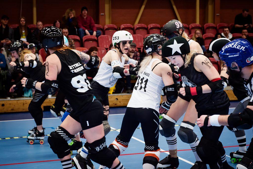 Halvbild på spelarna. Blockwork Orange i vita linnen försöker blocka Helltown Hellcats i svarta linnen.
