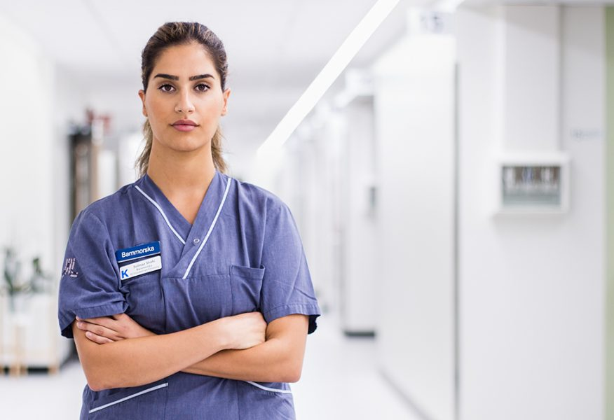Solmaz Shahi står i blå sjukskötersketröja med armarna i kors. Vit korridor i oskärpa bakom.
