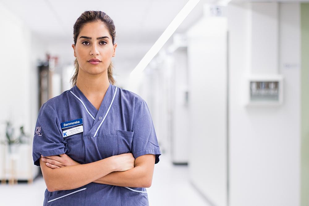 S står i blå sjukskötersketröja med armarna i kors. Vit korridor i oskärpa bakom.